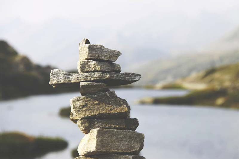 Stones stacked on top of each other in front of a lake